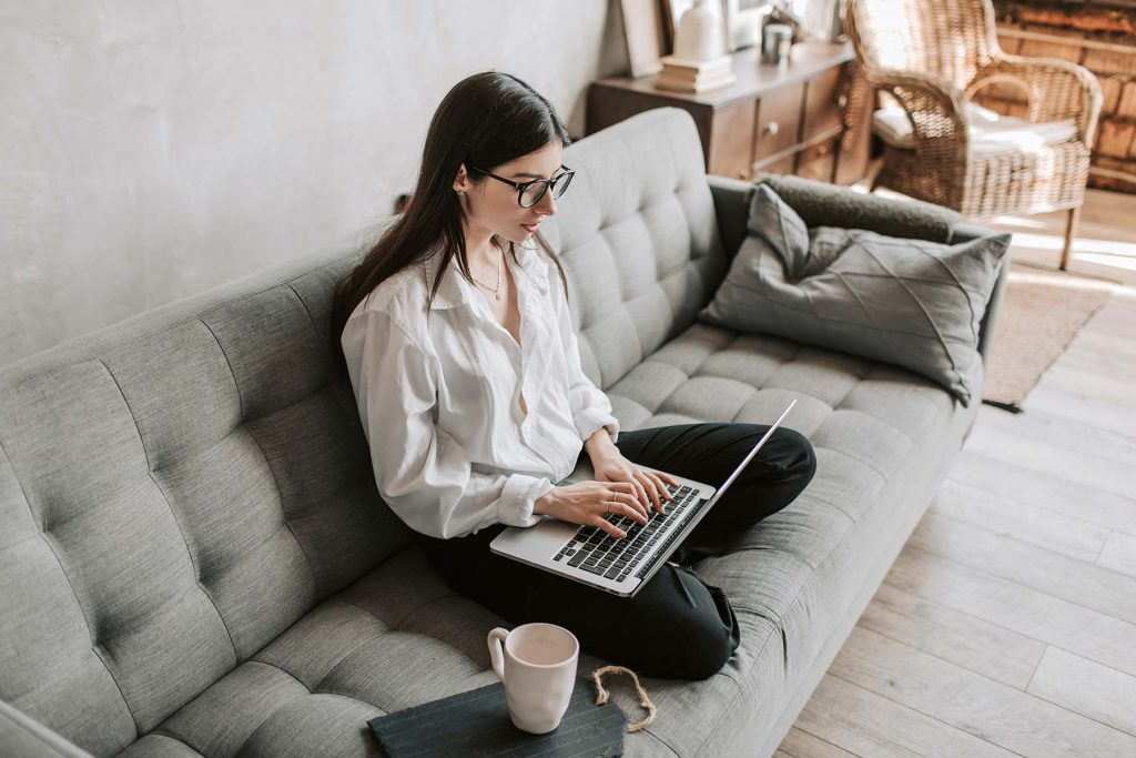 Woman sitting on a lounge using a laptop computer